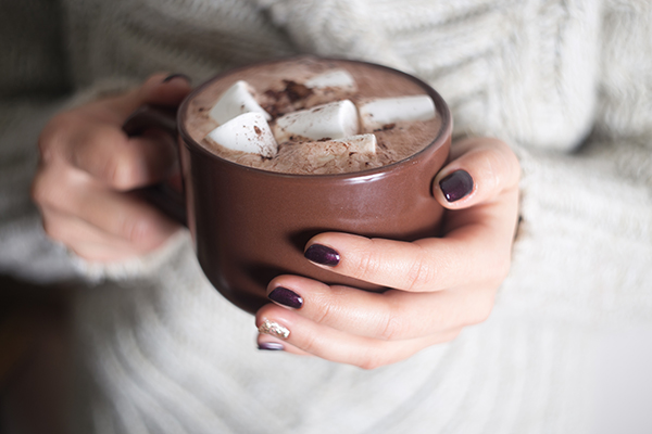 A mug with hot cocoa and marshmallow in the hands of the girl.