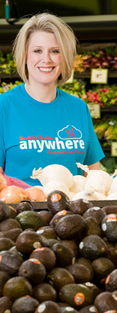 A smiling, middle-aged female Brookshire Brothers Anywhere employee in the produce section of the grocery store.