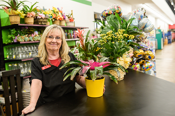 A Brookshire Brothers florist standing at a counter with a potted plant.