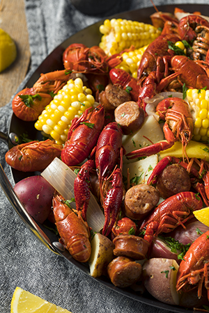 A southern crawfish boil with potatoes, sausage, corn, and other fixins in a large pot.