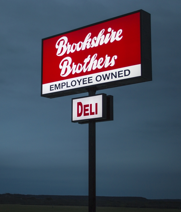 "A Brookshire Brothers sign with ""Employee Owned"" and ""Deli"" callouts against the evening sky."