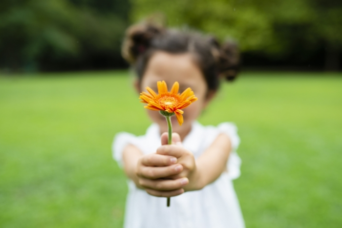 Young girl holding a sunflower