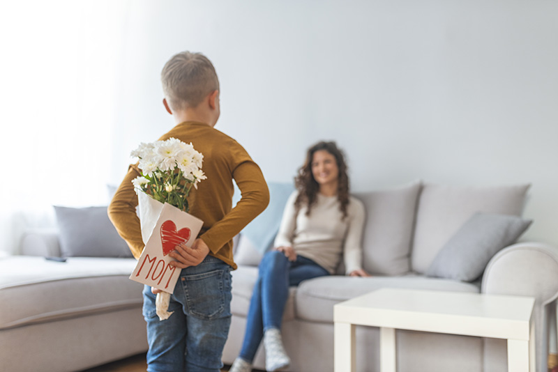 Boy holding flowers and a card for his mom on mother's day