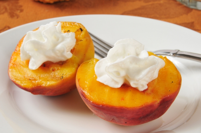 Lightly grilled peach halves with whipped cream