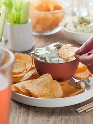 Platter of potato chips and fresh vegetables with dip.