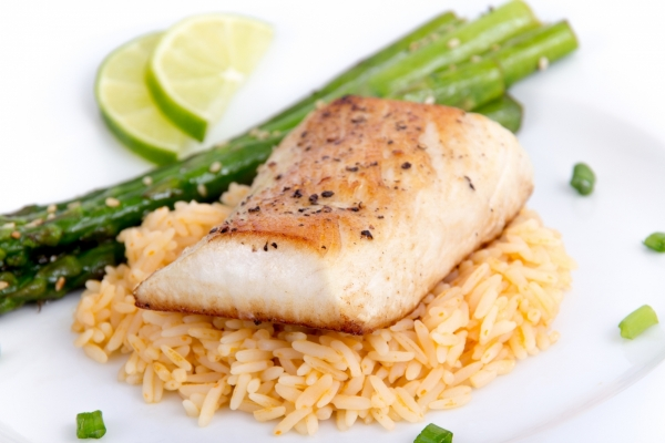 A broiled white fish on a bed of rice with a side of asparagus