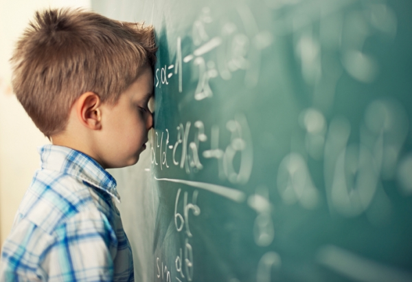 Little boy in math class overwhelmed by the math formula.