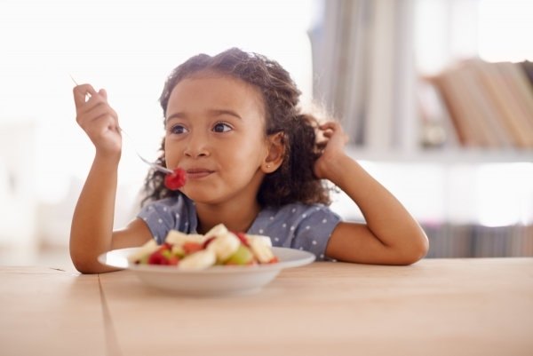 A young girl enjoying fruit salad at the table