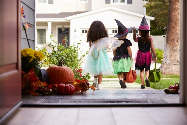 A group of three trick-or-treaters walking down the driveway