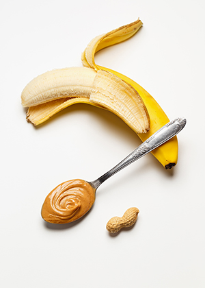 A halfway peeled banana with a spoonful of peanut butter