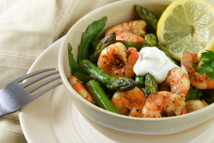 salad from prawn shrimp, green asparagus, arugula and lemon slice in a bowl on a plate, festive appetizer or buffet snack