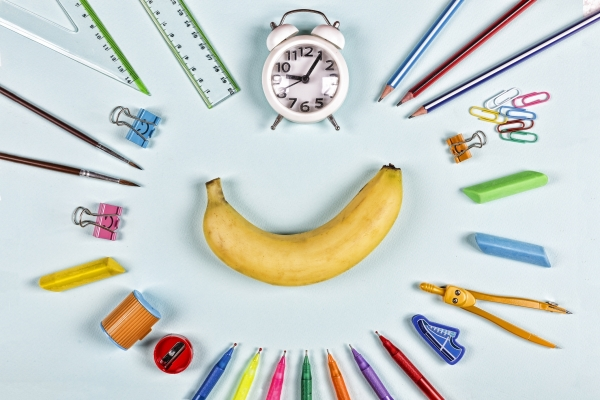 Back to school items laid out flat in a ring around a banana.