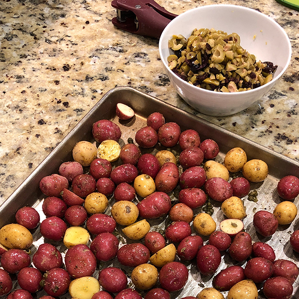 A pan of roasting potatoes next to a bowl of mixed ingredients.