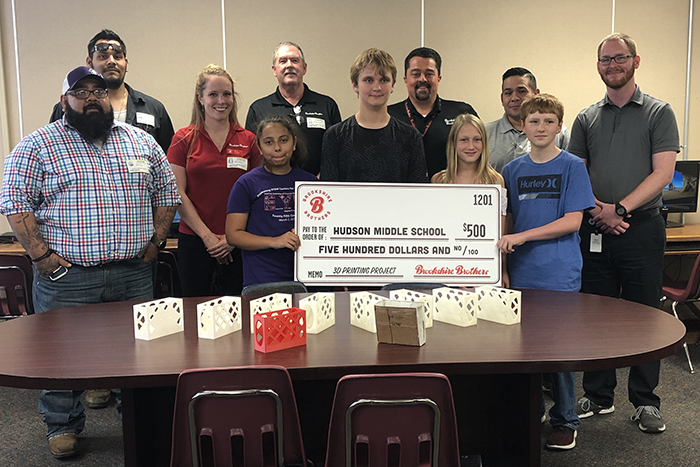 A group of Brookshire Brothers employees presenting a $500 donation to the students in Mr. Matheny's 3D Design class.