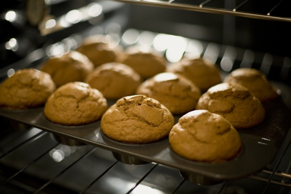 A pan of fresh-baked pumpkin muffins coming straight out of the oven.