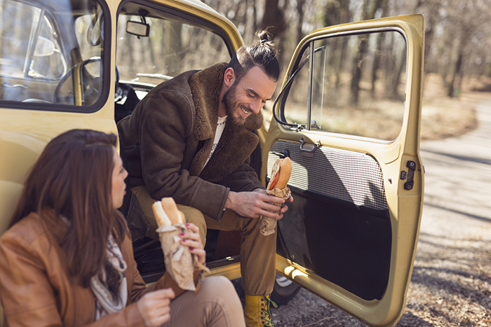 A man and woman take a lunch break with sandwiches outside their car on the side of the road