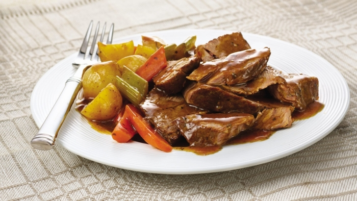 A delicious savory slow-cooked pot roast on a dinner plate.