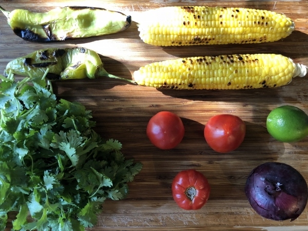 Salsa ingredients on a wooden background (corn, hatch chile, cilantro, tomatoes, onion, and lime)