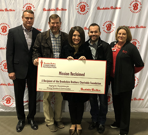 Brookshire Brothers CEO (John Alston) and CFO (Clay Oliver) stand with recipients from Mission Reclaimed, who hold a giant check representing the BBCF grant.